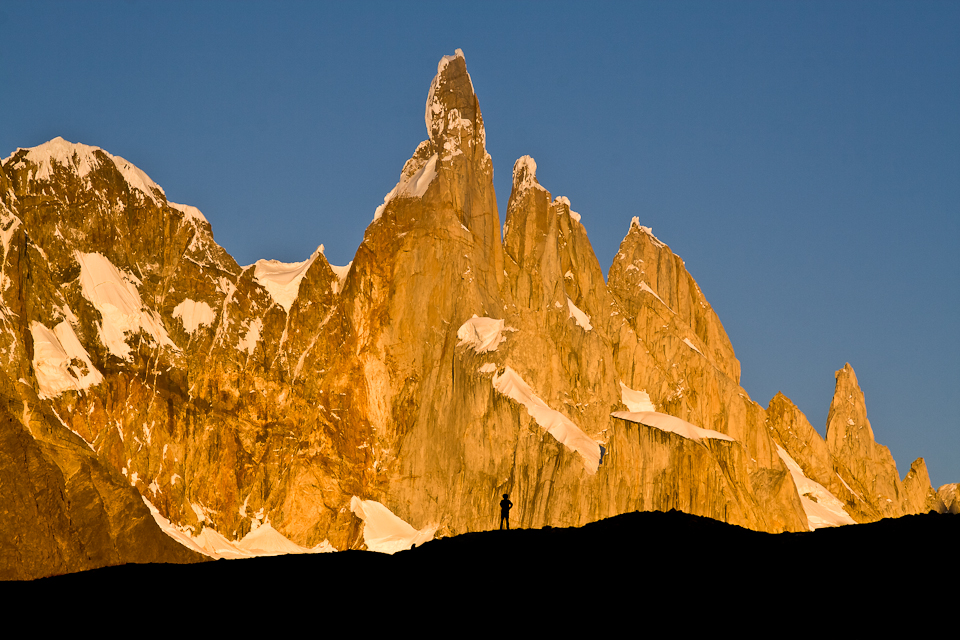 A hiker is silhouetted against Cerro Torre during sunrise on a bluebird sky day, Los Glaciares National Park, Patagonia, Argentina
