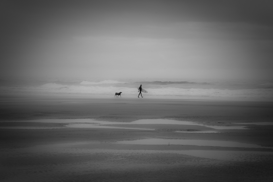 A surfer and his dog walk the beach at low tide, Cannon Beach, OR